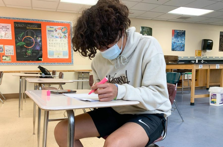 Junior Bennett Kouame catches up on homework during Park Connections May 14. Gov. Tim Walz said despite lifting the mask mandate, people will still be required to wear masks in school.