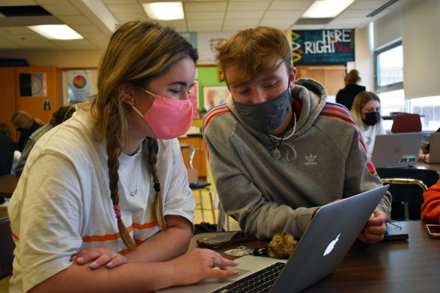 Junior Mason Boesche and sophomore Anna Becker look through photos May 11. Echowan is distributing yearbooks June 1 and 2.
