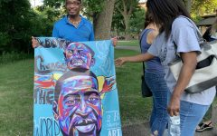 A Park resident holds up a tribute art piece for George Floyd June 6. The city held a memorial in commemoration of Floyd's life.