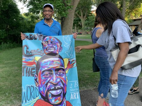 A Park resident holds up a tribute art piece for George Floyd June 6. The city held a memorial in commemoration of Floyd