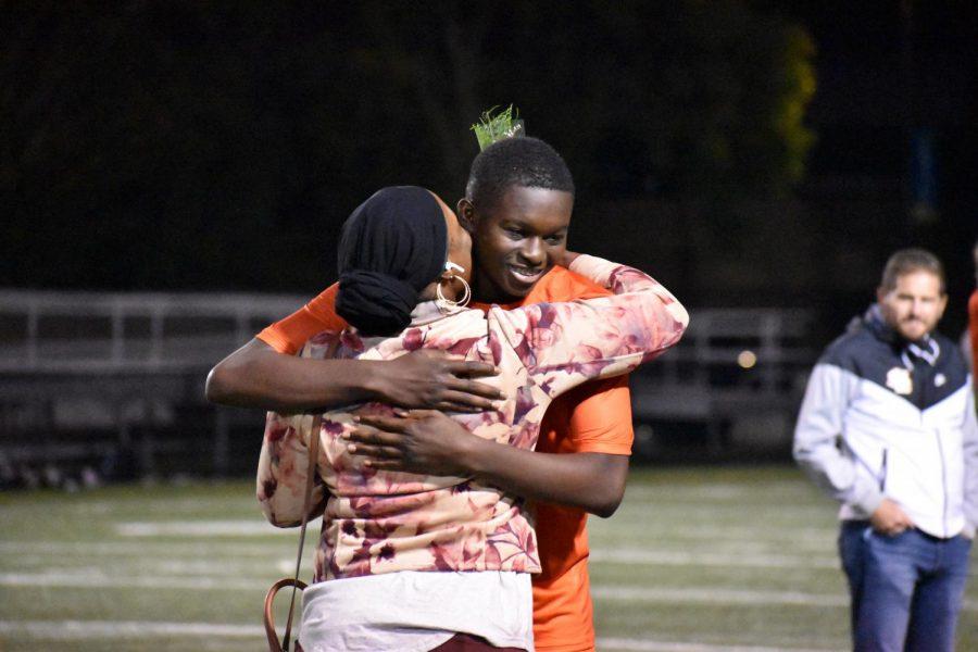 Senior Hassan Fofana hugs his mother Sept. 20. JV seniors played alongside varsity during this game.