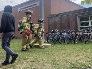 Firefighters walk to investigate the situation Sept. 30. Student were evacuated and stayed outside during the lunch period to ensure safety within the building.