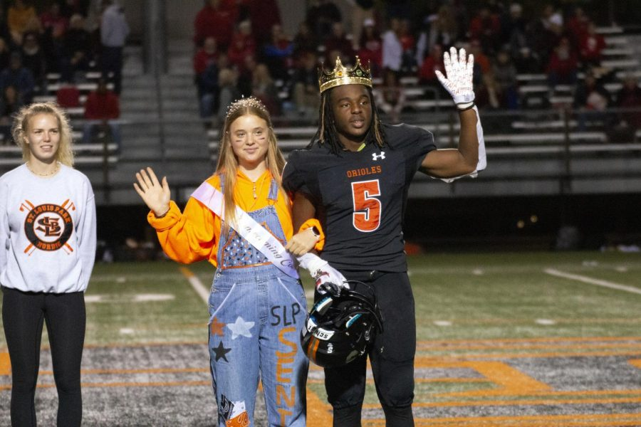 Senior Victoria Schmelzle and senior Ezra Hudson salute the crowd Sept. 25. Junior and senior royalty walked onto the field during halftime.