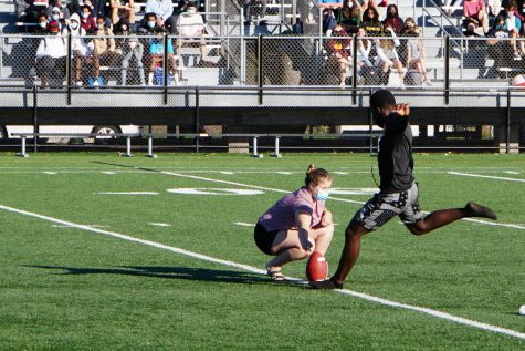 Senior Claudy Zua kicks a football at the pep fest Sept. 9. Fall captains encouraged students to come to their upcoming games.