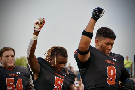 Seniors Ezra Hudson and Christain Artega raise their fists during the national anthem Sept. 10. Park beat Jefferson 26-20 in overtime.