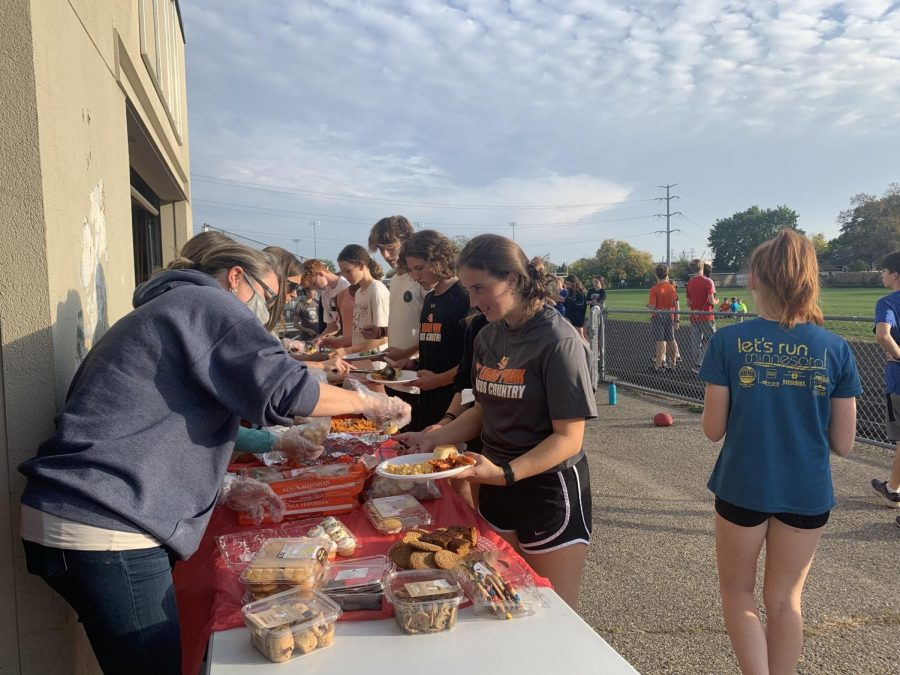 Junior Auden Whitlow gets food during a cross country pasta party Oct. 11. The team gathered in preparation for the Brookside Invitational which took place Oct. 12.