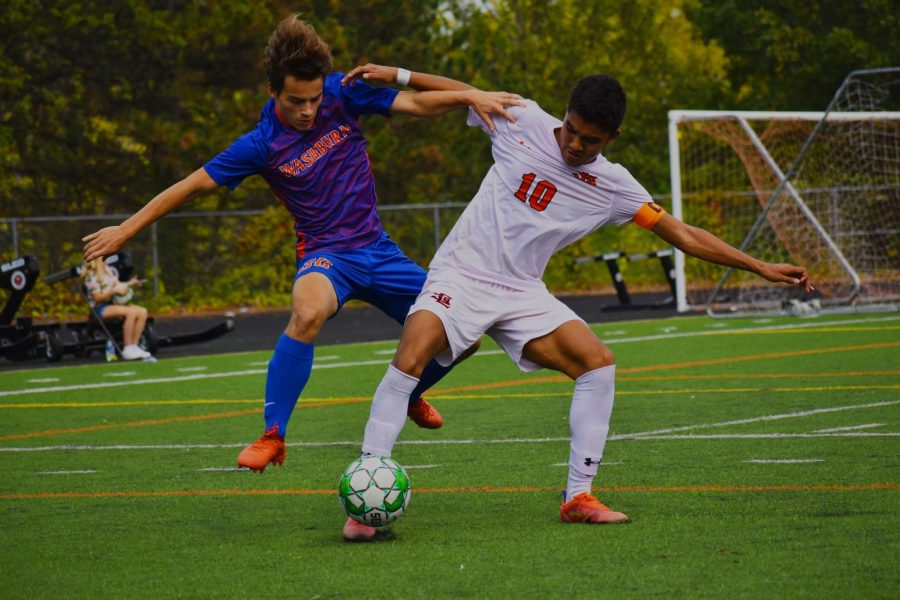 Senior captain Bennett Kouame and Washburn senior Ambrose Meyers fight for the control of the ball Oct. 9. Parks upcoming game will be their first sections match.