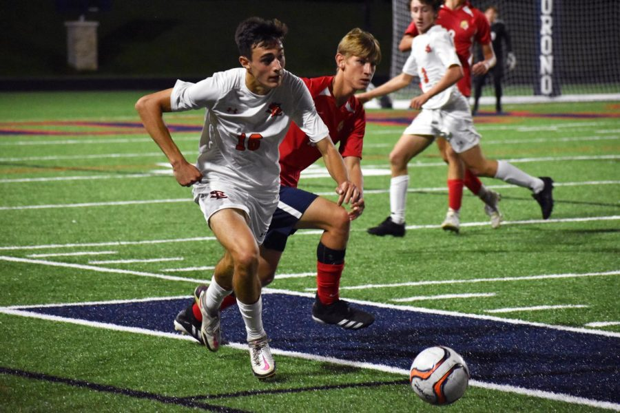 Junior Sebastian Tangleson successfully steals the ball from Orono forwarder Jaro Doise Oct. 5. According to head coach Chato Alvarez, it was a very competitive game and in the end they wanted the ball more than us.